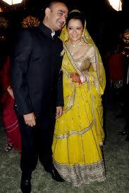 reema sen with her husband in a yellow lehenga choli